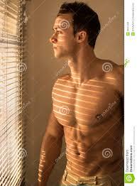 muscular shirtless man next to venetian blinds stock photo image