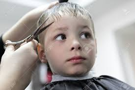 serious kid having a haircut at the barbershop stock photo