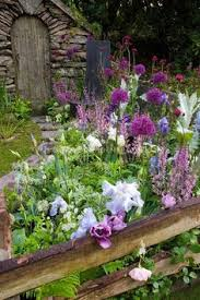 a pretty grass pathway leads to a garden gate flowers spill into