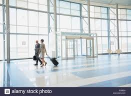 business people with suitcases in modern lobby stock photo