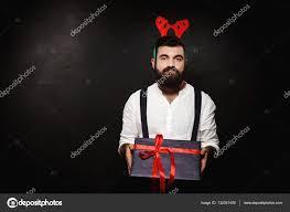man in fake deer horns holding christmas gift box over black