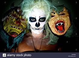 scary halloween photos free young woman in skull face paint between two scary halloween type