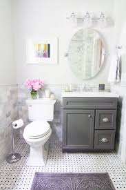 bathroom white closet toilet paper oval mirror black wood vanity