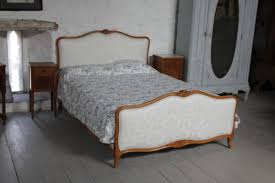 light brown linen fabric upholstered bed with headboard and brown