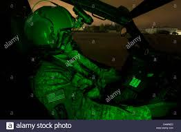 a pilot equipped with night vision goggles in the cockpit of an ah
