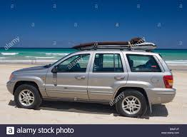 blue jeep grand cherokee silver jeep grand cherokee on the beach in australia surf boards