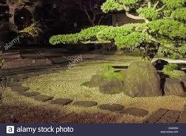 pine tree inside japanese zen garden with stone way around and