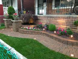 raised flower bed with decorative stone and a japanese maple by