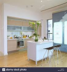 modern apartment kitchen with chrome stools at breakfast bar on