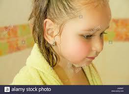 little beautiful girl playing taking a shower in bath with a stock photo little beautiful girl playing taking a shower in bath with a yellow bathrobe