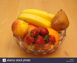 bowl of fruit oranges apples pear strawberries and bananas stock