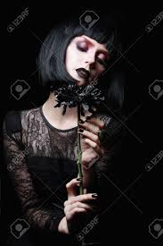 beautiful goth black flower in hand of young woman halloween