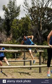 people jumping over the hurdles during obstacle course in boot