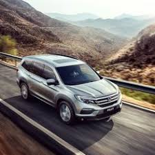 honda pilot commercial driving through what looks like barren land a large family
