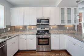 Stacked Stone Backsplash With White Cabinets And Hardwood Floors - White kitchen cabinets with white backsplash