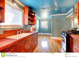blue kitchen with cherry cabinets and shiny floor stock photo