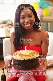portrait of young woman blowing out candle on birthday cake stock