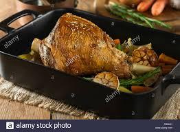 roast leg of lamb with garlic and rosemary in a roasting tray
