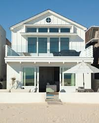 beach house roof exterior style with balcony outdoor lounge chairs