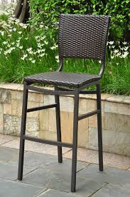 brown coated iron garden chair with wicker seating and ornate arms