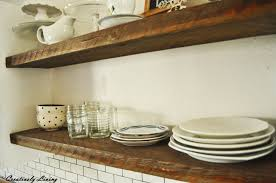 rustic open shelves in between cupboards creatively living