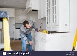 kitchen cabinet carpenter carpenter installing kitchen cabinet stock photo royalty free image