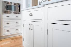 close up picture of painted white inset cabinets in a shaker style