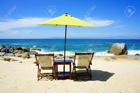 Chairs On A Beach Two Chairs A Table And A Yellow Umbrella On The Beach Stock Photo