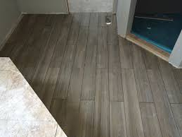 wood tile bathroom floor with penny tile shower floor showing