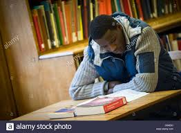 Picture Of Student Sitting At Desk by Male Black African American University Student Studying Book At