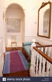 and rug and regency style sofa below large mirror