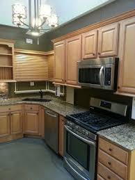 oak kitchen cabinets with stainless steel appliances light colored cabinetry with stainless steel appliances and