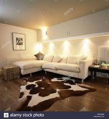 Corner Sofa In Living Room by Artificial Cowhide Rug In Modern Living Room With Down Lighting
