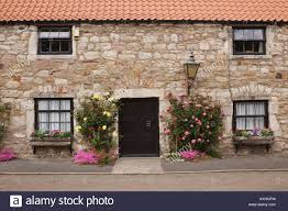 pretty stone cottage with climbing roses and flowers in wndow