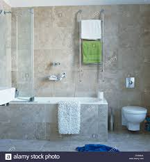towels on heated chrome rail on wall above bath with glass shower stock photo towels on heated chrome rail on wall above bath with glass shower screen and white bathmat in modern gray tiled bathroom