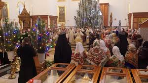 under a high christmas tree an orthodox church archbishop sits and