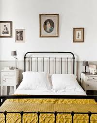 country style bedroom with vintage metal bed frame and wall arts