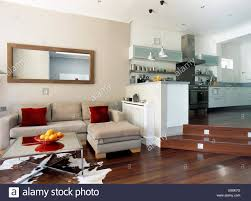 rectangular mirror above beige suede modular sofa in split level