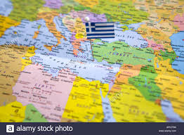 Greece On The Map by Flag Pin Placed On World Map In Rhodes Island Greece Stock Photo