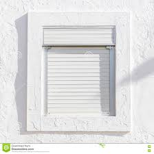 white window with white blinds on a white wall stock photo image