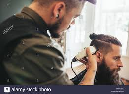 beard man getting haircut at barber shop hairdresser cutting hair