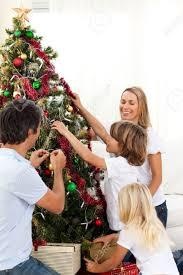 decorating christmas tree joyful family decorating christmas tree stock photo picture and