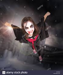 with face paint and halloween vampire costume flying stock