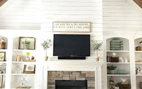 tv mounted over fireplace with exposed wires stovers