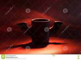 a halloween bat with a dark background cup of coffee as bat for halloween on black background red light