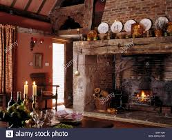 plates on large rustic wooden beam above inglenook fireplace with