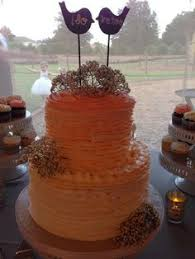 mountain themed wedding cake with blue ribbons and a monogram