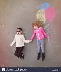 children are holding hands outside with colorful chalk balloons