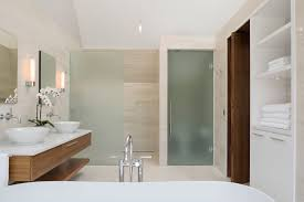 decorative framed glass panel door on white wooden bathroom wall