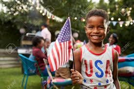 Black Flag Family Young Black Boy Holding Flag At 4th July Family Garden Party Stock